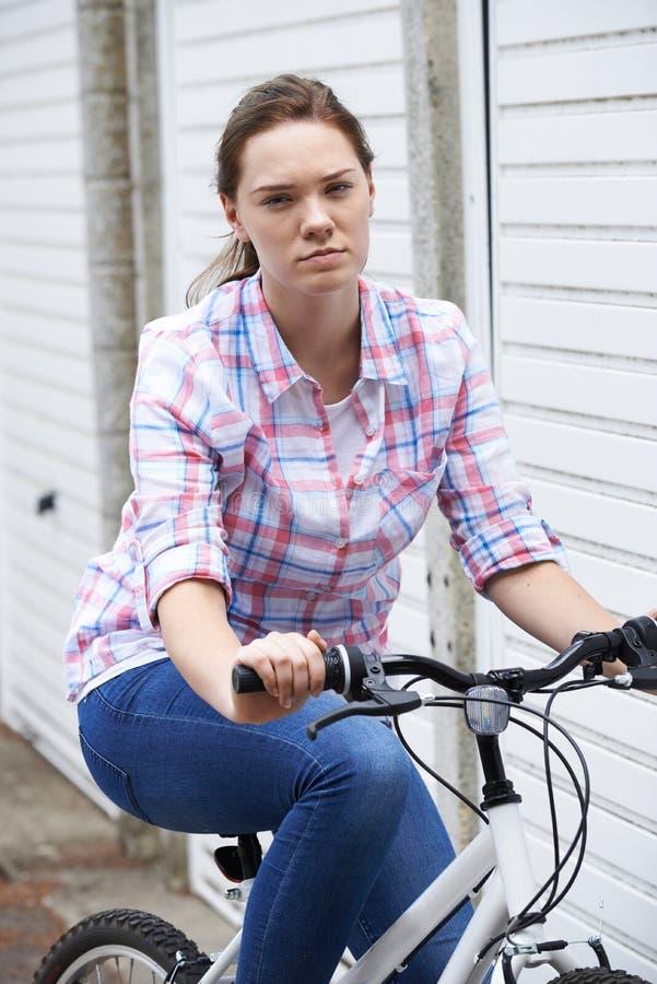 Stående av den olyckliga tonårs- flickan i ridningcykel för stads- inställning arkivfoto