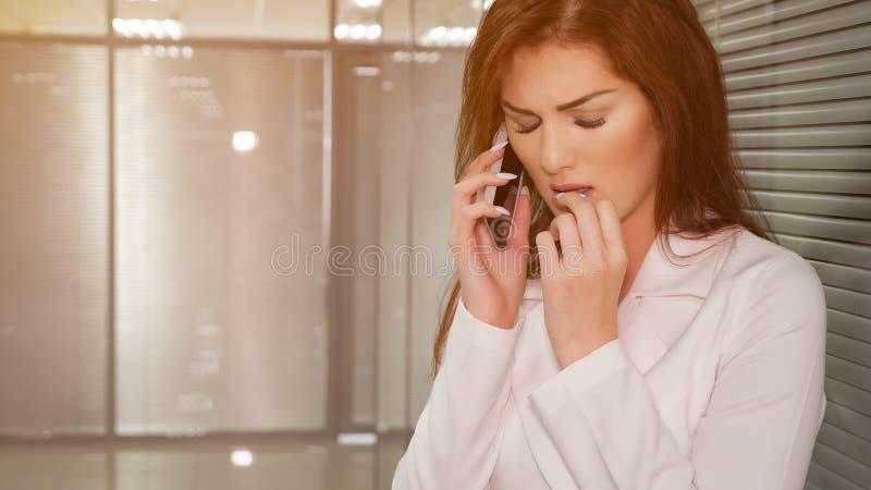 Stående av den olyckliga unga affärskvinnan som i regeringsställning talar på telefonen royaltyfri bild