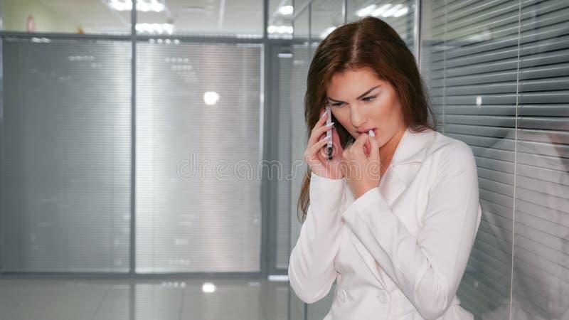 Stående av den olyckliga unga affärskvinnan som i regeringsställning talar på telefonen royaltyfria bilder