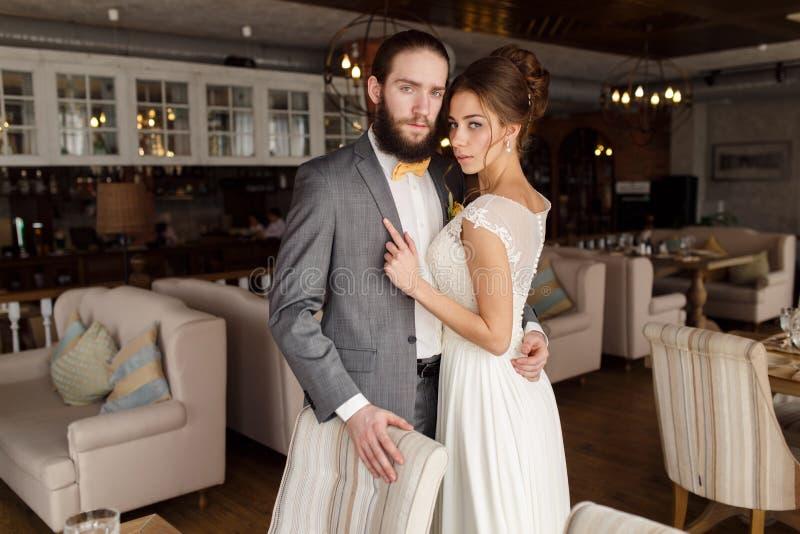 Stående av den omfamna bruden och brudgummen i en härlig inre fotografering för bildbyråer