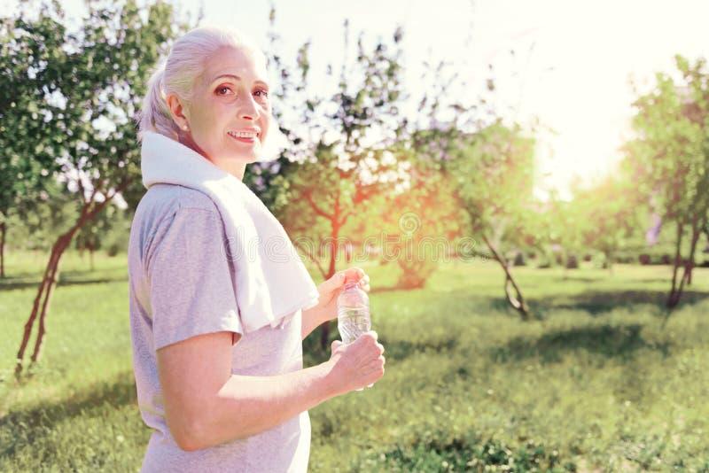 Stående av den optimistiska äldre kvinnan med en flaska av vatten arkivbild