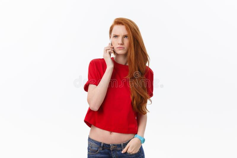 Stående av den optimistiska kvinnan i tillfällig kläder som talar på mobiltelefonen, medan stå isolerat över vit bakgrund arkivbild