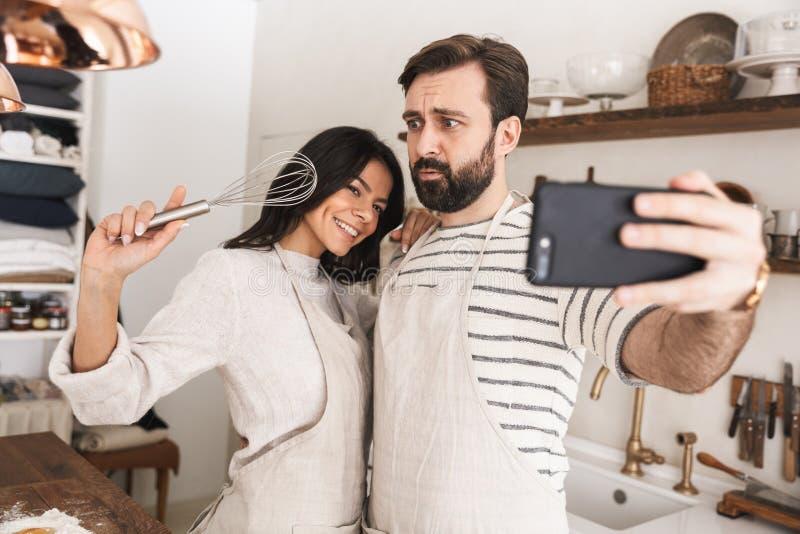 Stående av den optimistiska parman- och kvinna30-tal som bär förkläden som tar selfiefotoet, medan laga mat hemma royaltyfria bilder
