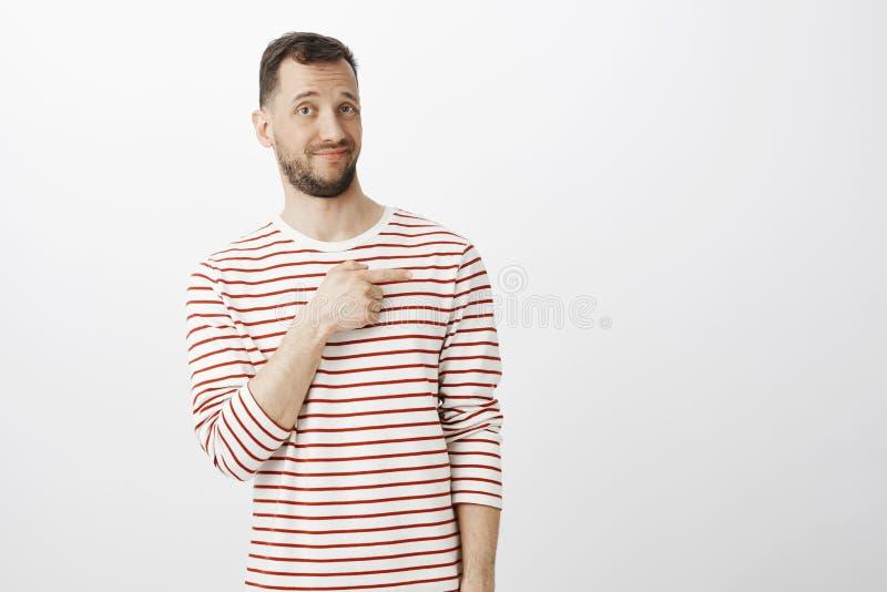 Stående av den osäkra tvekande attraktiva mannen med skägget som rätt pekar med pekfingret med missnöjt oberört royaltyfria foton