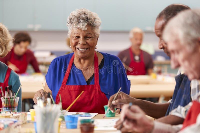 Stående av den pensionerade höga kvinnan som deltar i Art Class In Community Centre arkivfoton