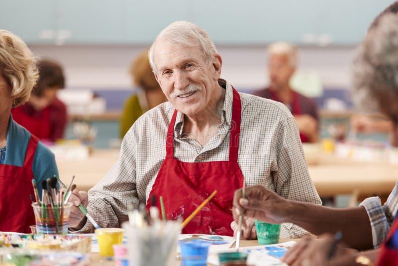 Stående av den pensionerade höga mannen som deltar i Art Class In Community Centre arkivbild