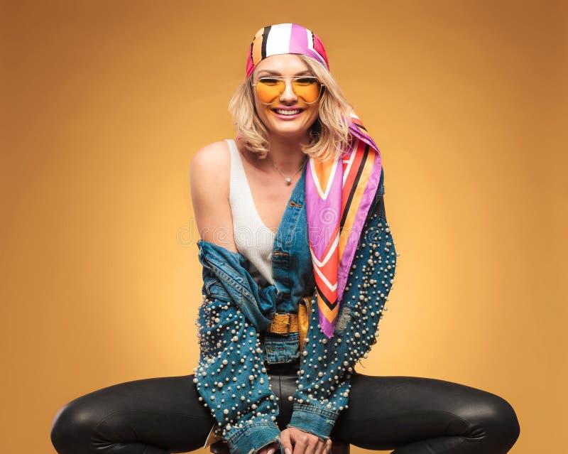 Stående av den placerade glade blonda kvinnan som bär färgrik kläder royaltyfri bild