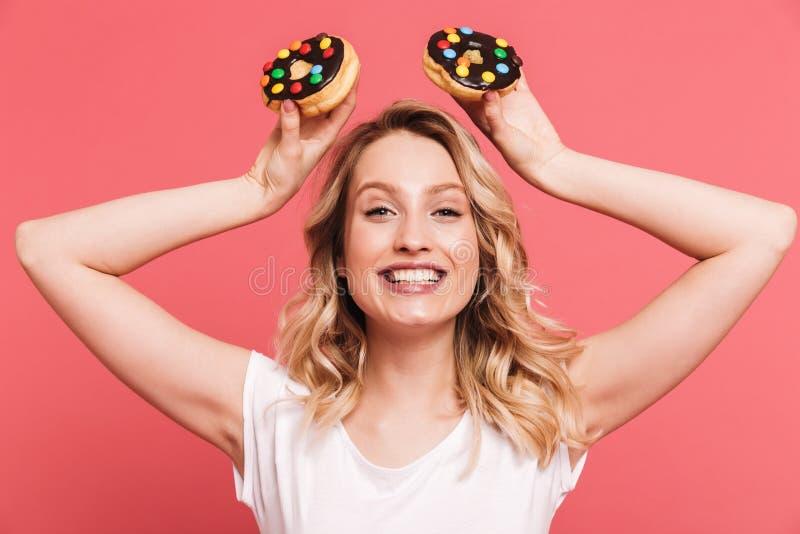 St?ende av den positiva blonda kvinna20-tal som b?r den tillf?lliga t-skjortan som ler, medan rymma smakliga s?ta donuts royaltyfria bilder