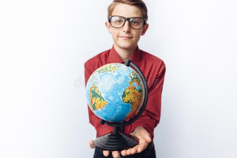Stående av den positiva och emotionella skolpojken, med jordklotet, vit bakgrund, exponeringsglas, röd skjorta, affärstema, adver arkivfoton