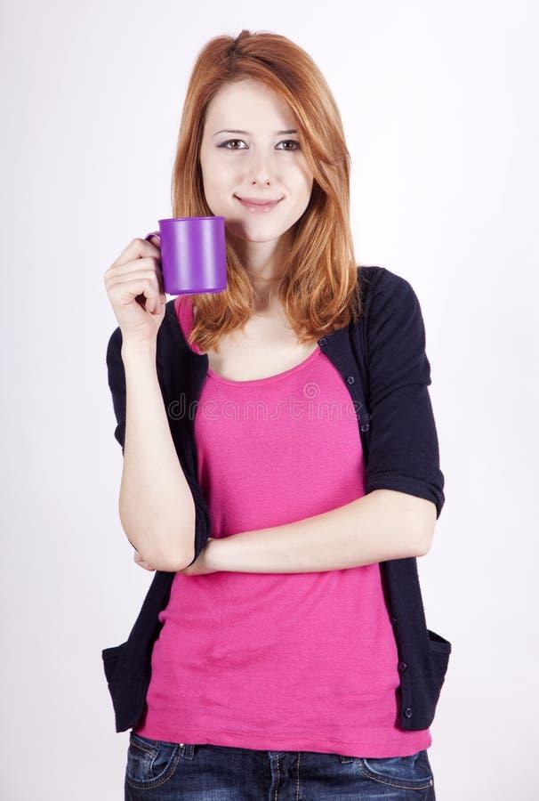 Stående av den rödhåriga flickan med koppen. arkivbilder