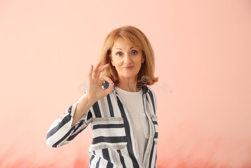 Stående av den reko gesten för mogen kvinnavisning på färgbakgrund arkivfoto