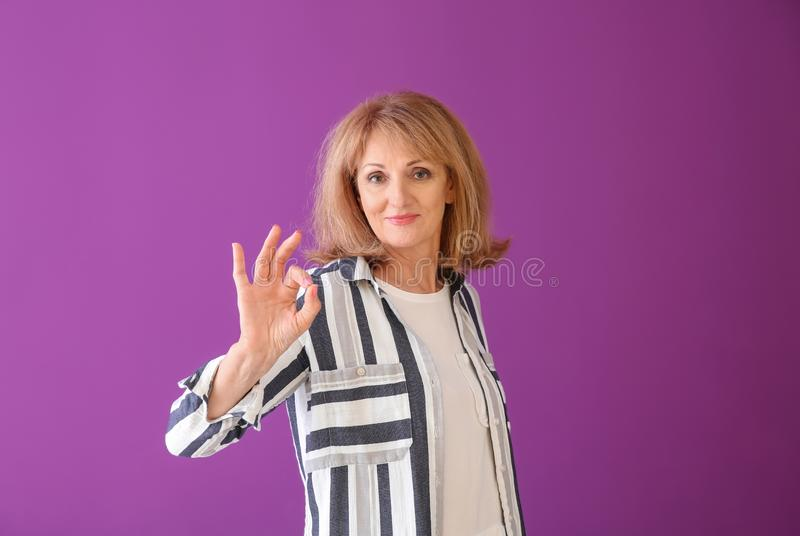 Stående av den reko gesten för mogen kvinnavisning på färgbakgrund arkivbilder
