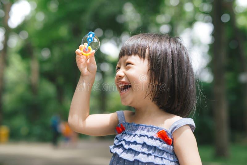 Stående av den roliga älskvärda lilla flickan som blåser såpbubblor royaltyfria foton