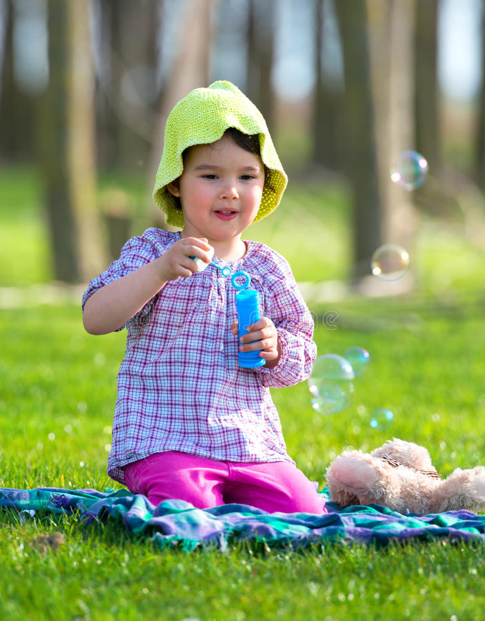 Stående av den roliga älskvärda lilla flickan som blåser såpbubblor i parkera royaltyfri foto