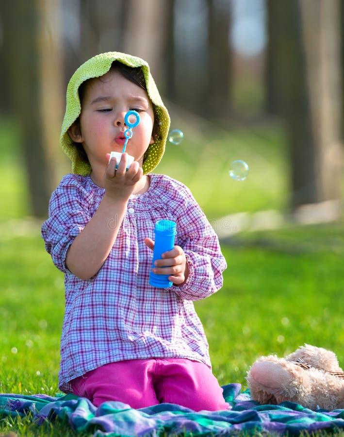 Stående av den roliga älskvärda lilla flickan som blåser såpbubblor i parkera royaltyfria bilder