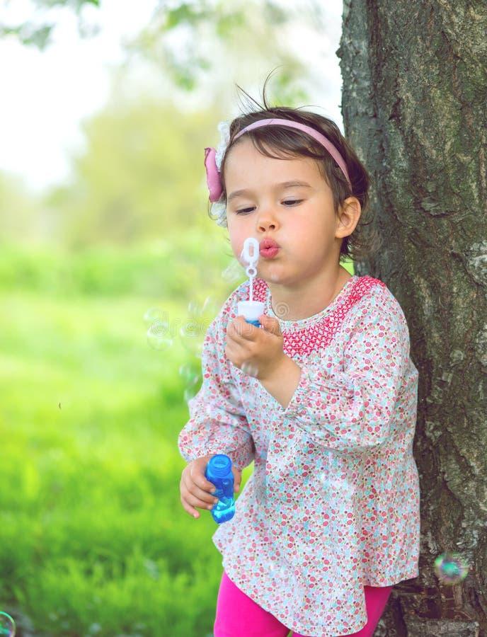 Stående av den roliga älskvärda lilla flickan som blåser såpbubblor i parkera royaltyfria foton