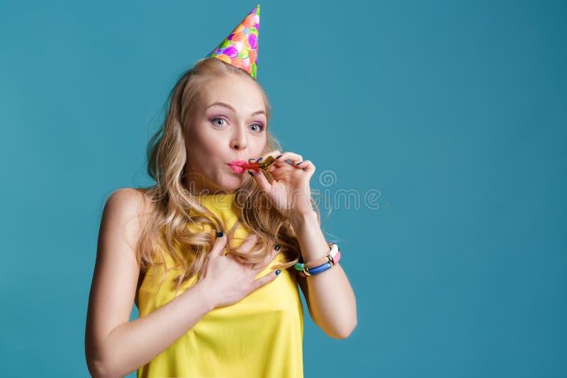 Stående av den roliga blonda kvinnan i födelsedaghatt och gulingskjorta på blå bakgrund Beröm och parti arkivfoto