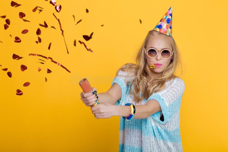 Stående av den roliga blonda kvinnan i födelsedaghatt och röda konfettier på gul bakgrund Beröm och parti royaltyfria bilder