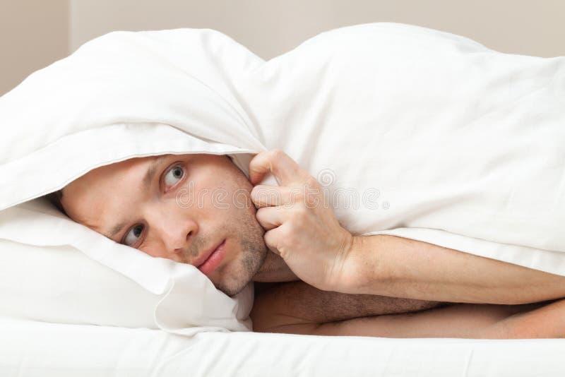 Stående av den roliga förskräckta unga mannen i säng arkivfoton