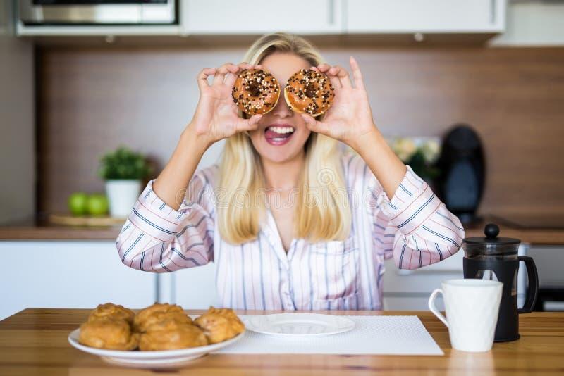 Stående av den roliga flickan som täcker henne ögon med donuts i modernt K royaltyfri bild