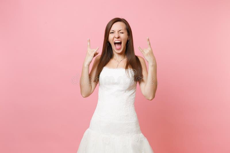Stående av den roliga galna brudkvinnan i den vita bröllopsklänningen som står blinka och visa vagga-n-rulle tecknet som isoleras fotografering för bildbyråer