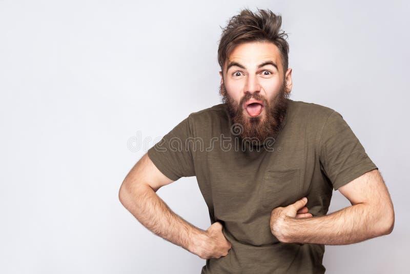 Stående av den roliga galna skäggiga mannen med tungan ut och mörker - grön t-skjorta mot ljus - grå bakgrund royaltyfria foton