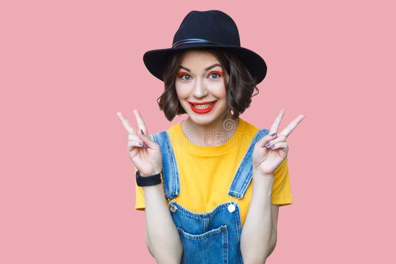 Stående av den roliga härliga unga flickan i den gula t-skjortan, blåa grov bomullstvilloveraller, makeup, hattanseende med fred  arkivfoto