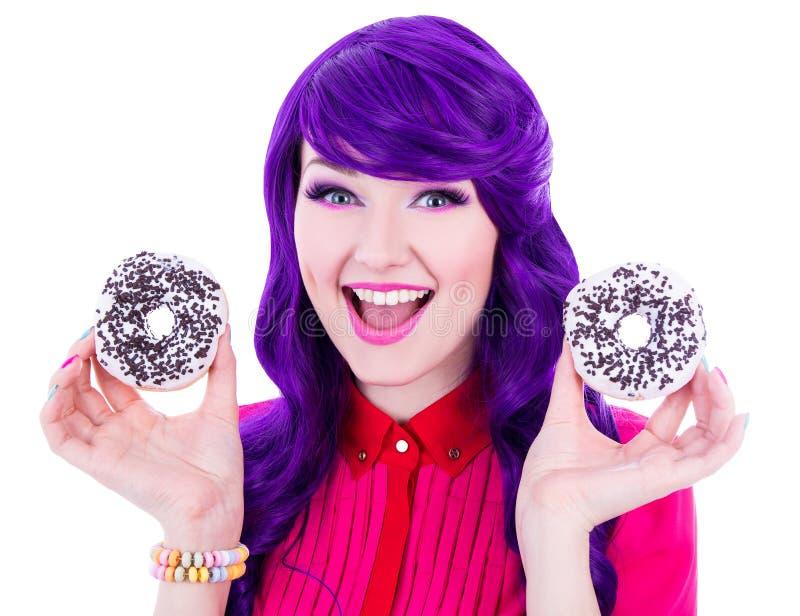 Stående av den roliga kvinnan med purpurfärgat hår och två donuts arkivfoto