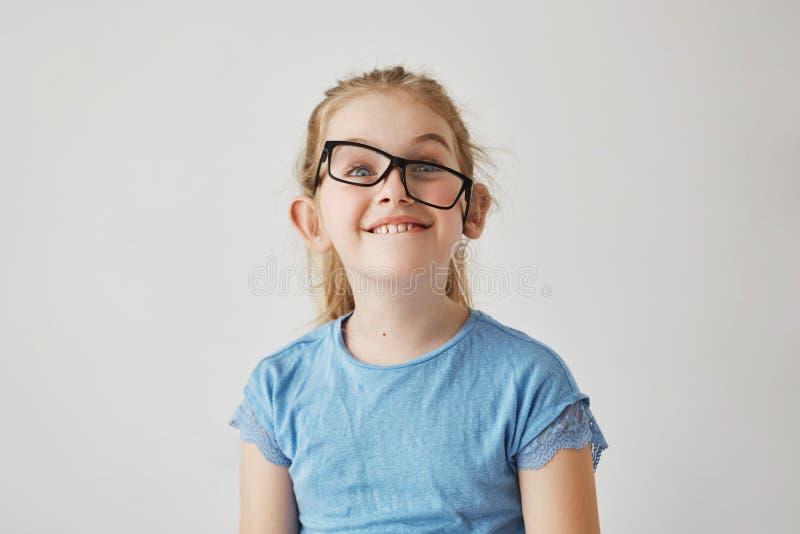 Stående av den roliga lilla flickan med blåa ögon och ljust hår i den blåa skjortan som har gyckel med exponeringsglas för fader` arkivfoto