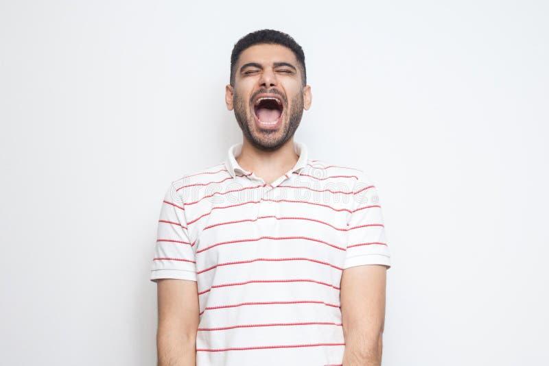 Stående av den roliga stiliga skäggiga unga mannen i randigt t-skjorta anseende med stängda ögon och att skratta royaltyfri fotografi