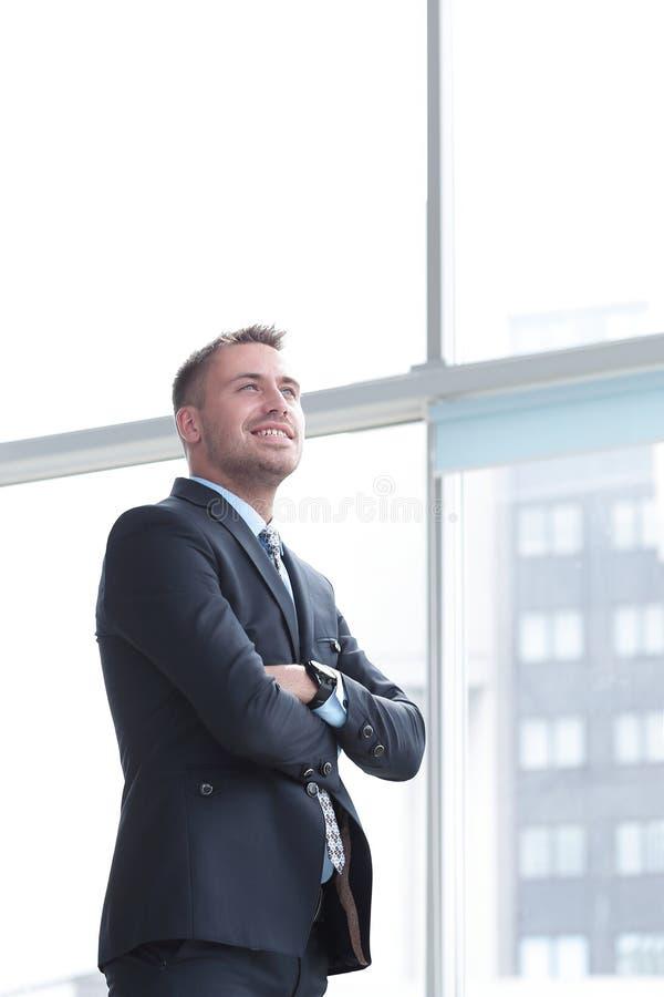 Stående av den säkra affärsmannen som ut ser fönstret av kontoret arkivbilder