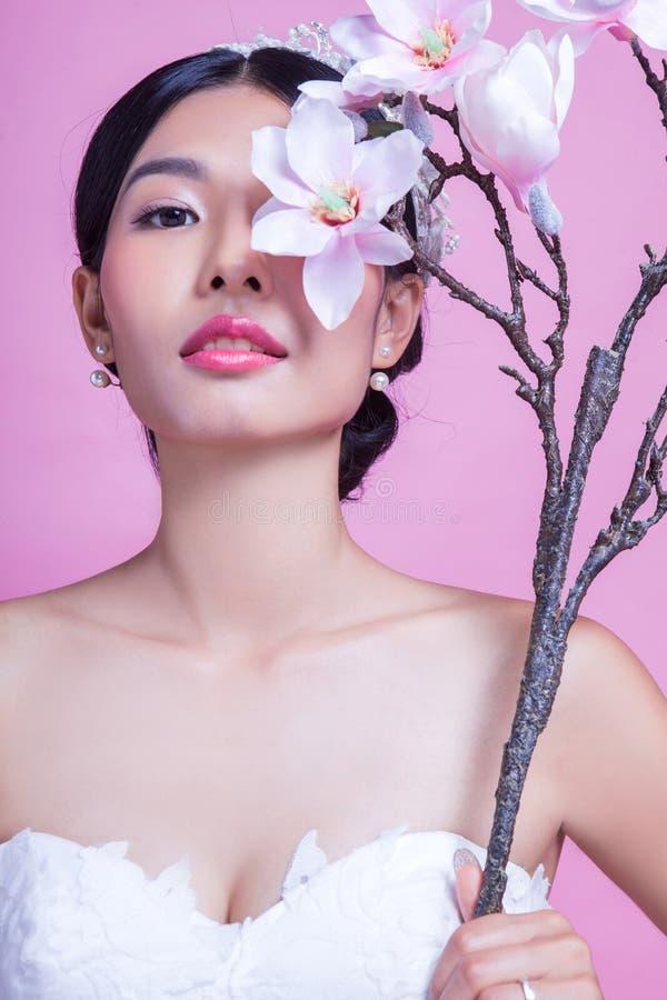 Download Stående Av Den Säkra Bruden Som Rymmer Konstgjorda Blommor Mot Rosa Bakgrund Arkivfoto - Bild av kulört, glamour: 78732326