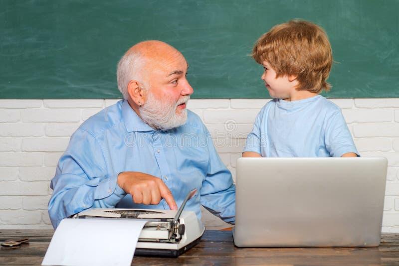 Stående av den säkra gamla manliga läraren Lärare som hjälper hans tonåriga elev på utbildningsgrupp Ung pojke som gör hans skola arkivbild