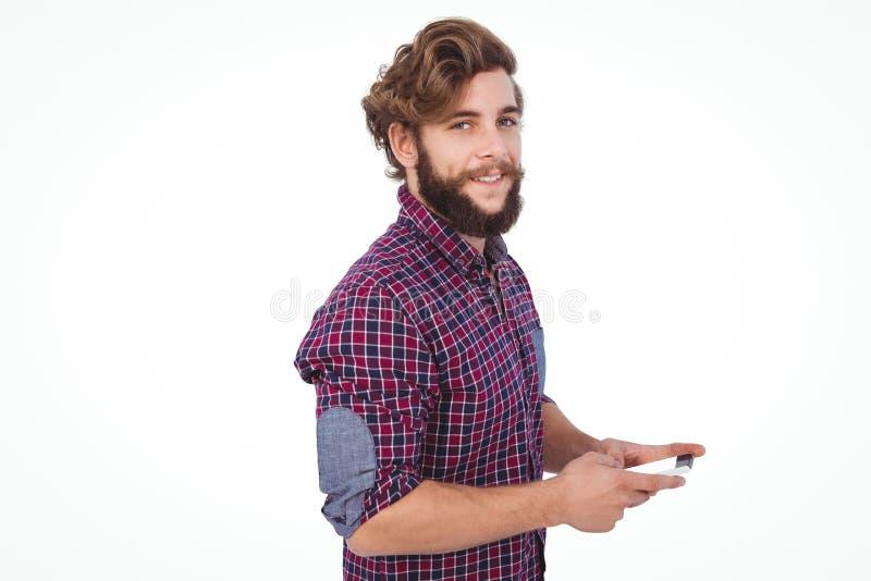 Stående av den säkra hipsteren som använder smartphonen royaltyfria foton