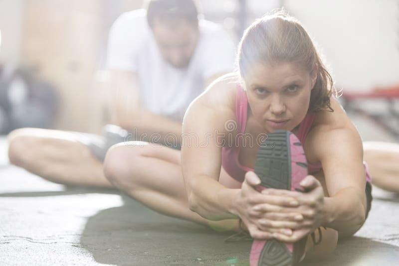 Stående av den säkra kvinnan som gör sträcka övning i crossfitidrottshall arkivfoton