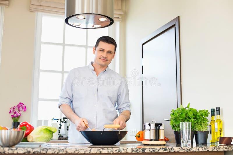 Stående av den säkra mannen som förbereder mat i kök arkivbild