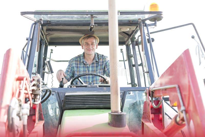 Stående av den säkra mogna bonden som kör traktoren på lantgården arkivbild