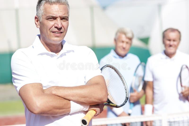 Stående av den säkra mogna mannen som rymmer tennisracket, medan stå med armar som korsas mot vänner på domstolen under solig dag fotografering för bildbyråer