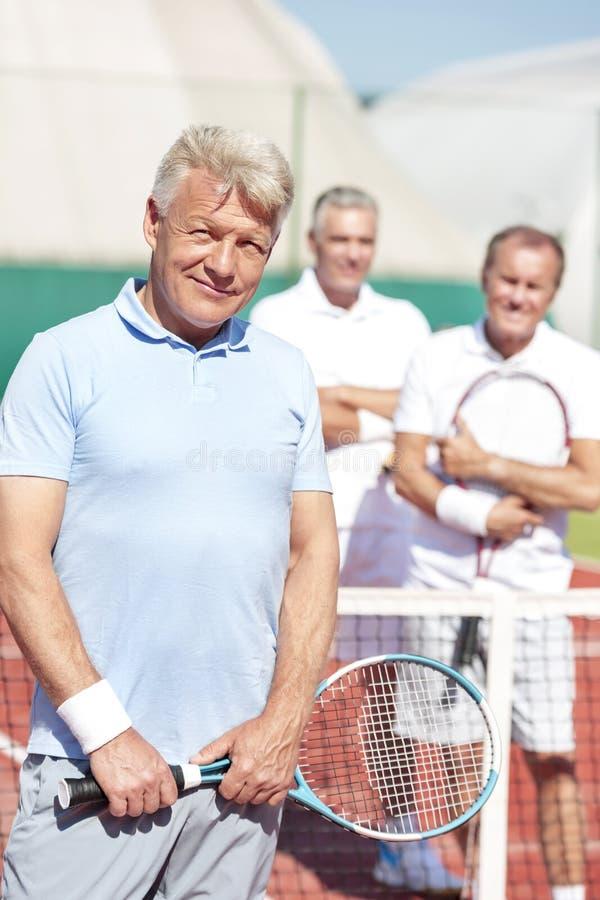 Stående av den säkra mogna mannen som rymmer tennisracket, medan stå mot vänner på domstolen under solig dag royaltyfri foto