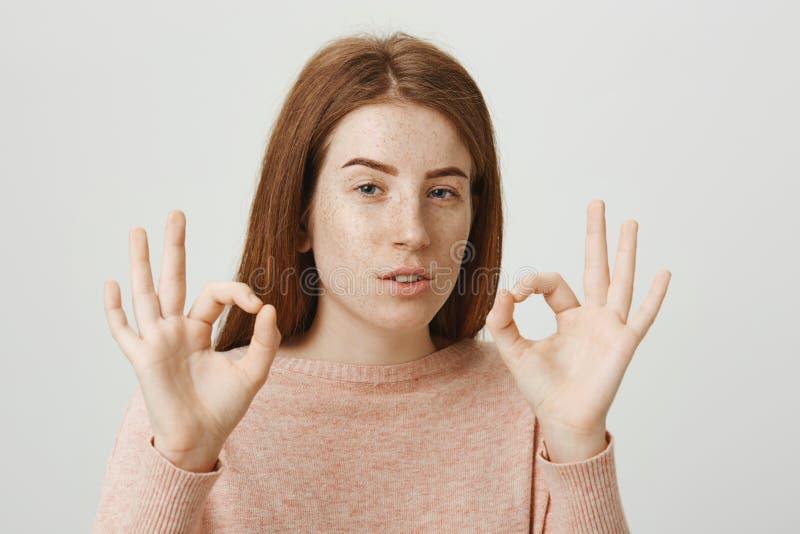 Stående av den säkra och misstänksamma rödhårig mankvinnan med fräknar som bra skelar och visar eller fint tecken som står royaltyfri fotografi