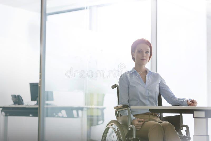 Stående av den säkra rörelsehindrade affärskvinnan som i regeringsställning sitter på skrivbordet fotografering för bildbyråer