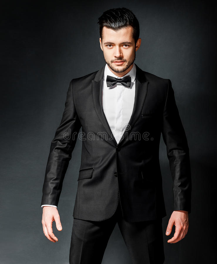 Stående av den säkra stiliga mannen i svart dräkt med bowtie fotografering för bildbyråer