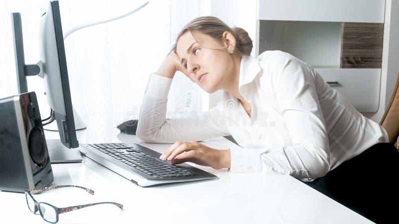 Stående av den sömniga unga kvinnan som ser datorbildskärmen arkivfoton