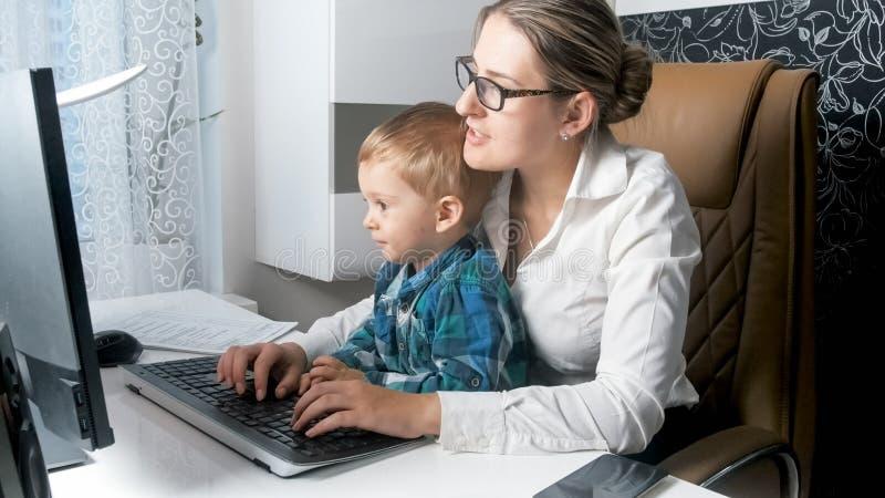 Stående av den selfemployed affärskvinnan som hemifrån arbetar med hennes kontor för barn arkivbilder