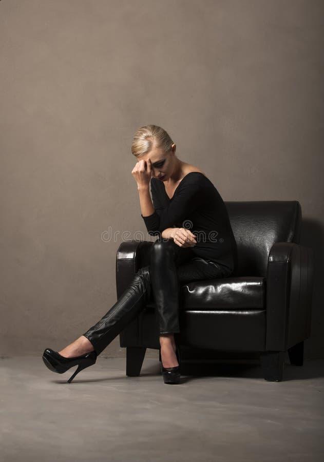 Stående av den sexiga blonda kvinnan som placeras i stol royaltyfri bild
