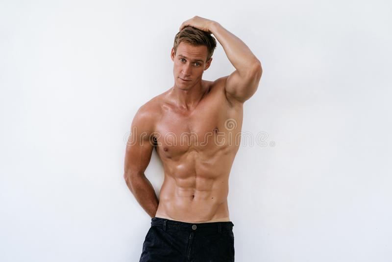 Stående av den sexiga idrotts- mannen med den nakna torson på vit bakgrund Stilig grabb med den muskulösa kroppen royaltyfria foton
