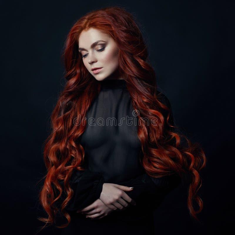Stående av den sexiga kvinnan för rödhårig man med långt hår på svart backgroun royaltyfria bilder