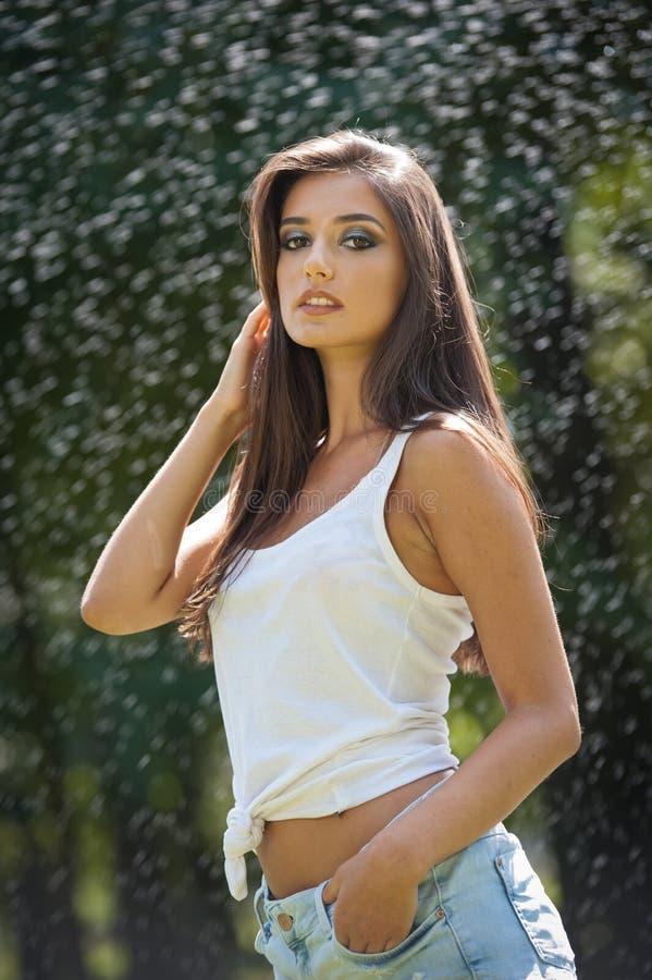 Stående av den sexiga kvinnan i sprej av vatten med den vita T-skjortan Hon har ett bra att stilla hud, sinnlig ställing, och hon royaltyfria bilder
