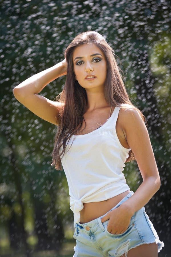 Stående av den sexiga kvinnan i sprej av vatten med den vita T-skjortan Hon har ett bra att stilla hud, sinnlig ställing, och hon royaltyfri fotografi