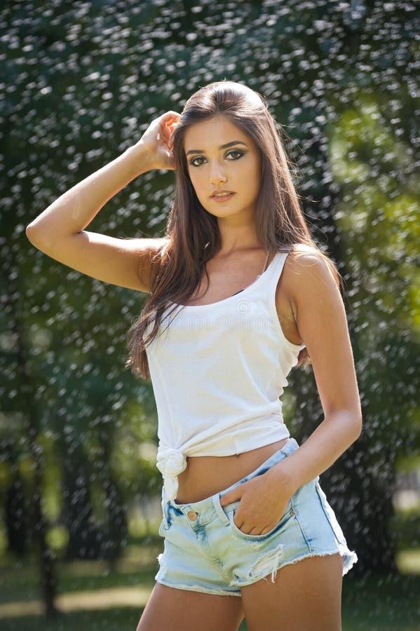 Stående av den sexiga kvinnan i sprej av vatten med den vita T-skjortan Hon har ett bra att stilla hud, sinnlig ställing, och hon fotografering för bildbyråer